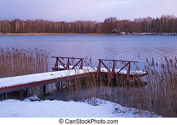 Old wooden pier on the lake in winter evening time.