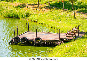 old wooden pier on the pond with green water