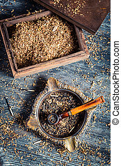 Old wooden pipe with tobacco in an ashtray