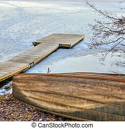 Old wooden rowboat and pier in the frozen lake