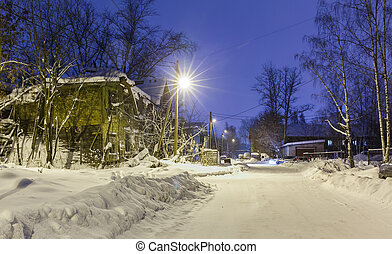 old wooden ruined barracks at winter night