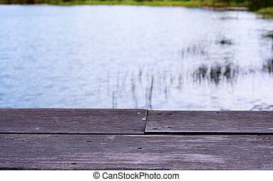 old wooden seat at riverside with light on water