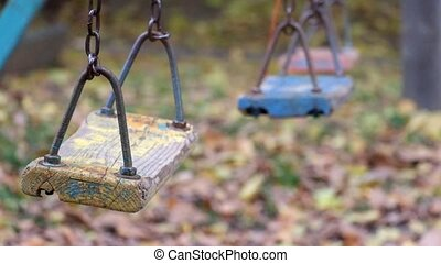 Old wooden shabby childrens swing swayed by itself