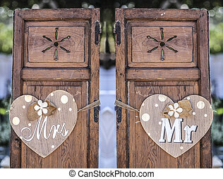 Old wooden shutter windows with hanging hearts for Mrs and Mr