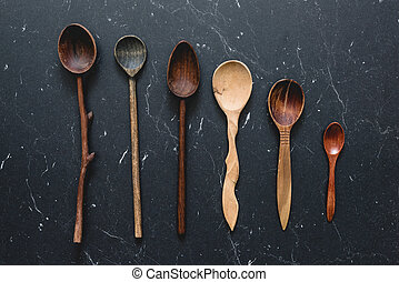 Old wooden spoons on dark background