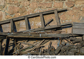 Old wooden staircase, sticks and chips on backyard under house stone wall background
