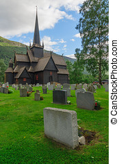 Old wooden stave chapel surrounded by cemetery, Norway