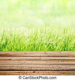 Old wooden table on green grass background. Shallow depth of...