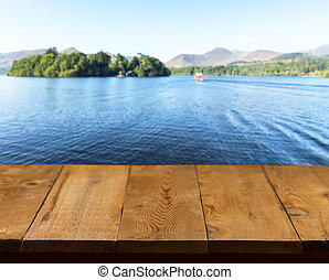 Wood pier or walkway or an old wooden table with blurred image of lake district in England as background