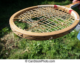Old wooden tennis racket with torn strings