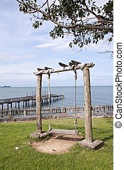 Old wooden vintage swing with sea view