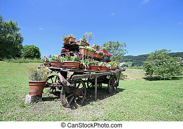 old wooden wagon decorated with many pots