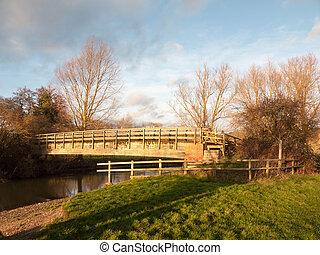 old wooden walking bridge over water sunset landscape