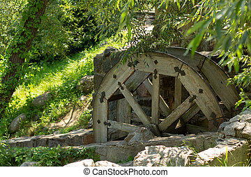 old wooden water pumping wheel on the river
