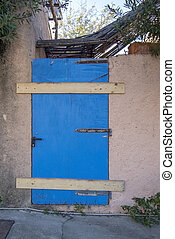 Old wooden weathered door painted blue closed with wood panels