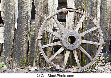 Old wooden wheel from a cart on wooden fence background. Copy space