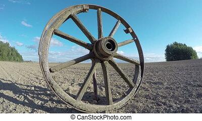 old wooden wheel in the field