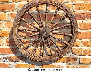 Old wooden wheel on a brick wall.