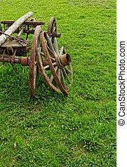 old broken wooden wheel spokes, side by chariot