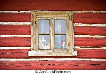 Old wooden window in the wall of cottage with few dolls inside