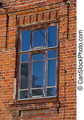 Old wooden window in the wall of red brick