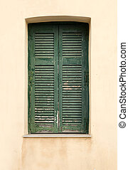 Old wooden window with green shutters.