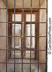 Old wooden window with iron bars black