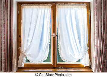 Old wooden window with white curtains in a traditional house in
