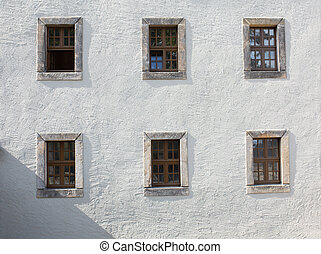 Old wooden windows on the wall outside of building