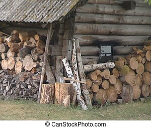 Old wooden woodshed made of logs with slate roof at the lake...
