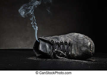 Old work shoe in smoke - Old black work shoe from which the...