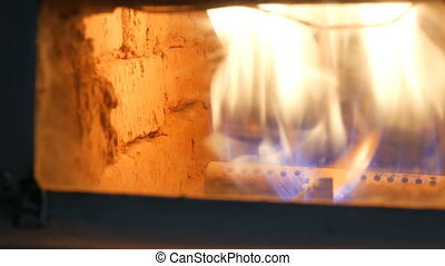 Old working gas fireplace in which a flame of fire burns