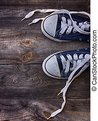 Old worn blue sneakers with white laces untied