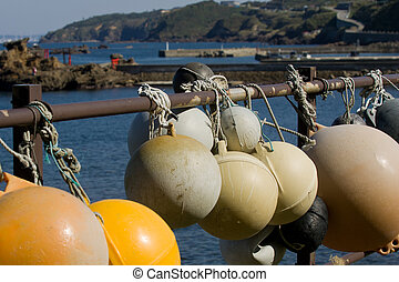 Old worn fishing bouys in the sun with a Japanese Harbour in...