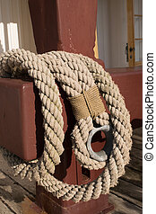 Old worn rope on a red pole