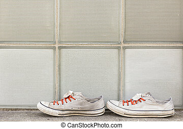 Pair of old worn classic sneakers for travel or point of view background