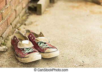 Pair of old worn classic sneakers leaning against a brick wall