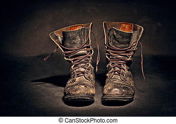 old soldier's boots worn with scratches and untied shoelaces on white background