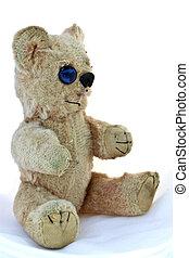 Old worn teddy bear on white background