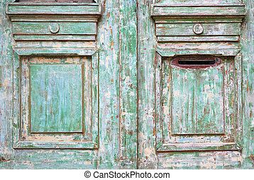 Old worn wooded door with green paint peeling off