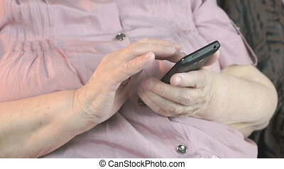 Old wrinkled hands holding mobile phone. Close up