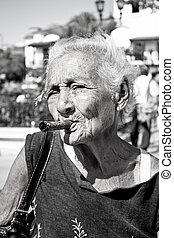 Old wrinkled woman with red flower smoking cigar. Cuba - Old...