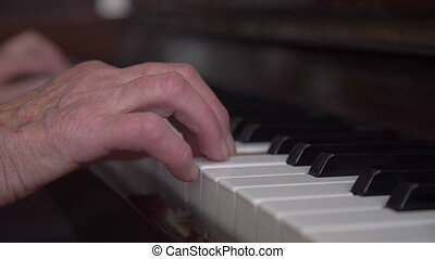 Old wrinkled woman's hands starting to play the piano