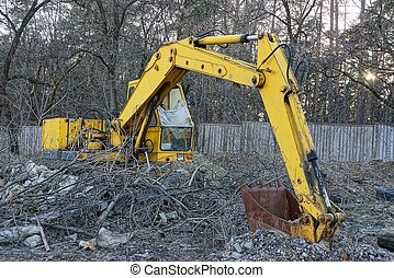 old yellow excavator with a rusty bucket stands outside in the dry vegetation