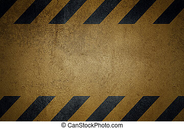 Old yellow grungy metal plate surface with black warning stripes