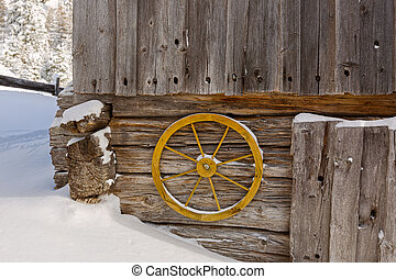 Old yellow wagon wheel hanging on wall to decorate rustic wooden barn, snow winter in Austria, Europe