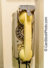 Old yellow wall-mounted rotary telephone