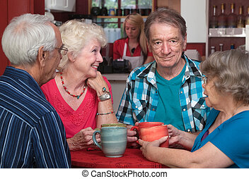 Elderly white adults in a happy conversation at a cafe