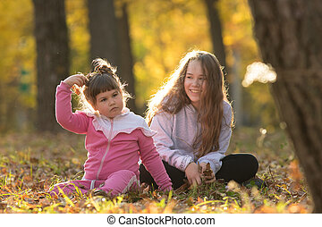 Older and little sisters sitting on the ground in autumn park