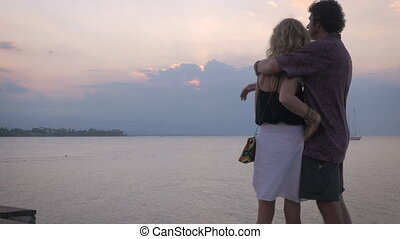 Older beautiful couple embrace while overlooking a sunset over the ocean